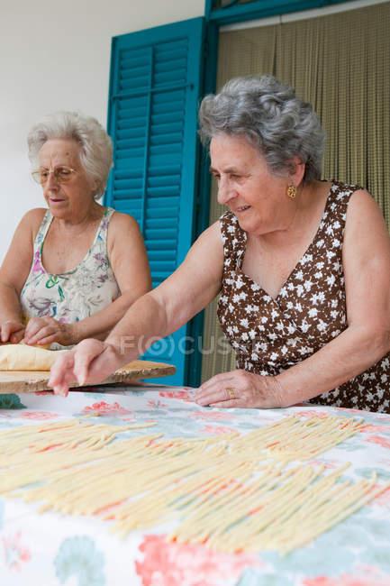 Donne anziane che fanno la pasta insieme, focus selettivo — Foto stock