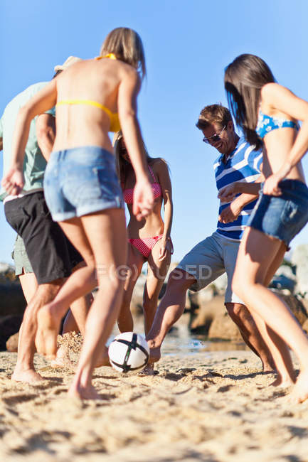 Friends playing soccer on beach, selective focus — Stock Photo