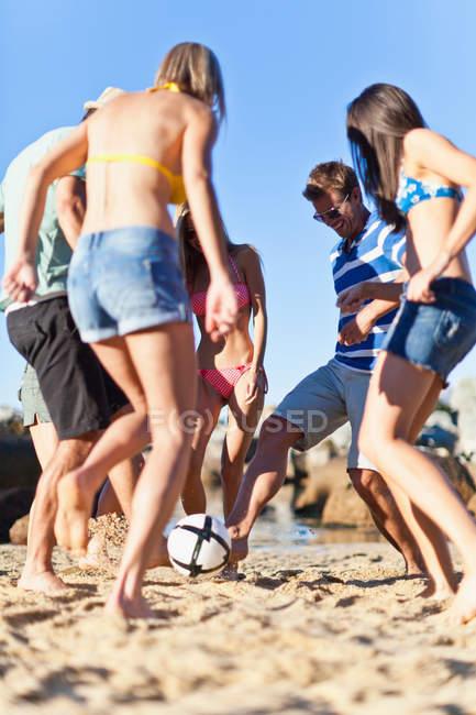 Друзья играют в футбол на пляже, избирательный фокус — стоковое фото