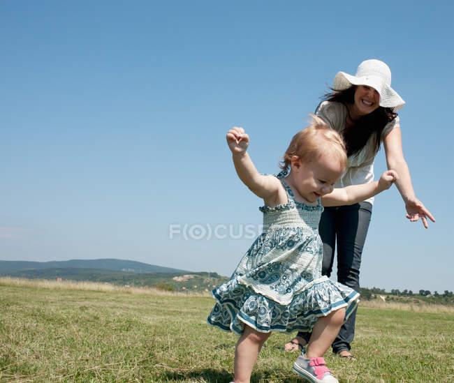 Madre e hija caminando en el campo - foto de stock