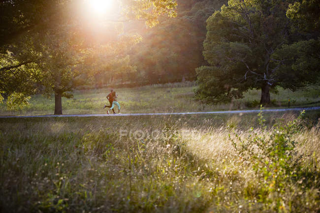 Young couple running in sunlit in park — Stock Photo