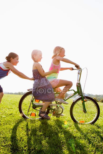 Meninas brincando com bicicleta na grama — Fotografia de Stock