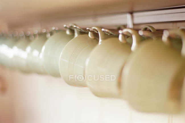 Cups hanging on rack — Stock Photo