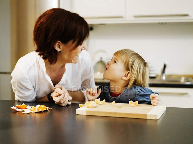 Madre e hija pelando naranja - foto de stock