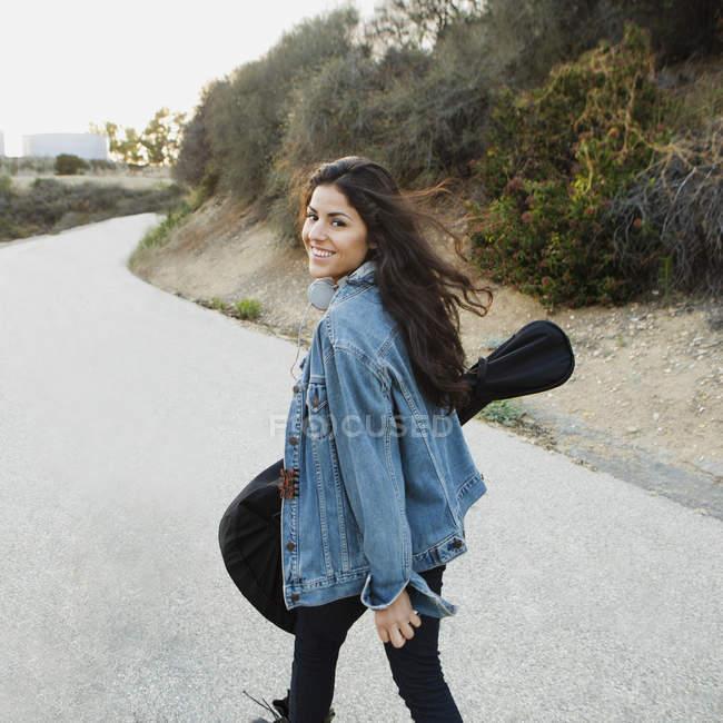 Молодая женщина, несущая гитару, смотрит через плечо на камеру и улыбается, Вудленд Хиллс, Калифорния, США — стоковое фото