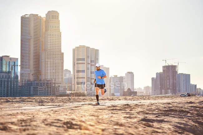 Mid adult man running on sand by skyscrapers, Dubai, United Arab Emirates — Stock Photo