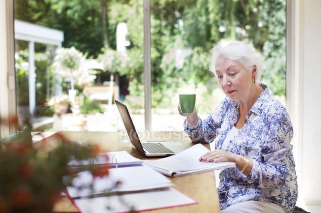 Donna anziana seduta a tavola, che guarda tra le scartoffie — Foto stock