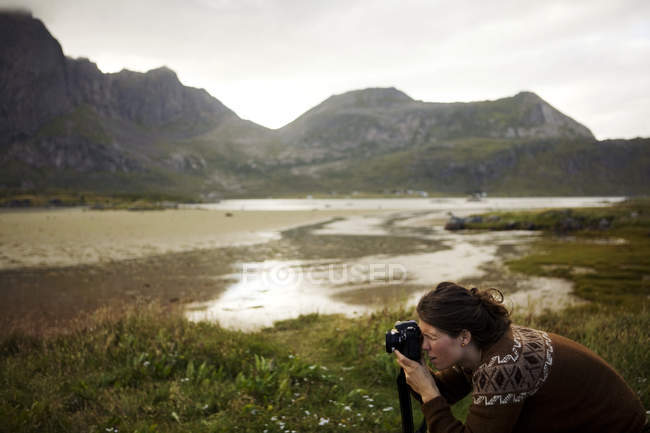 Woman taking a photograph in mountain landscape — Stock Photo