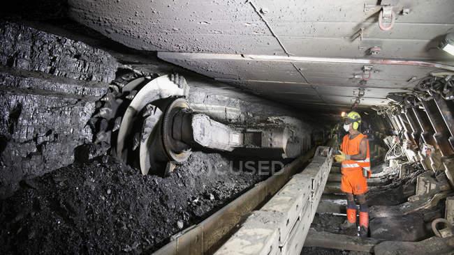 Miner cutting coal at coal seem in deep mine — Stock Photo