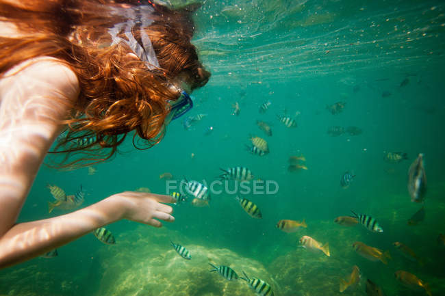 Girl snorkeling in tropical waters — Stock Photo