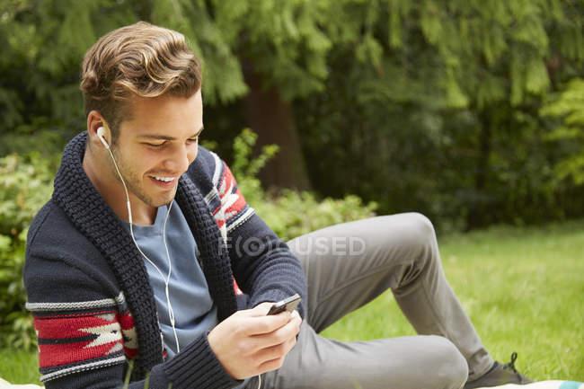 Portrait of man laying in garden listening to smartphone wearing earphones — Stock Photo