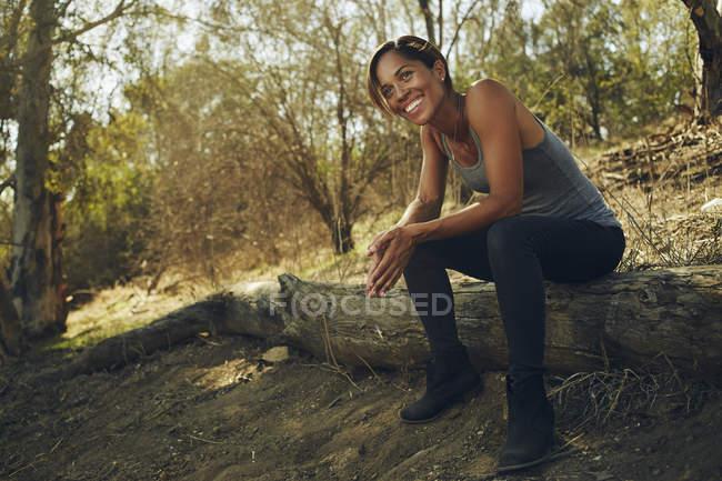 Heureuse femme assise sur une colline — Photo de stock