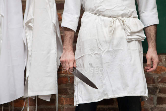 Cropped image of Butcher standing with knife — Stock Photo