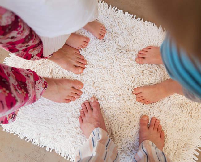 Family feet on white bath mat — Stock Photo