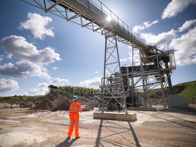 Ouvrier debout à côté de la machine de criblage et de concassage de pierre dans la carrière — Photo de stock