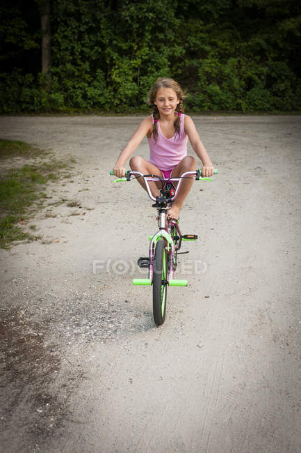 Front view of girl balancing on bike, legs raised, looking at camera smiling — Stock Photo