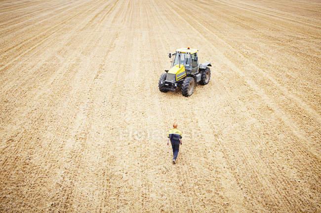 Farmer walking to tractor in crop field — Stock Photo