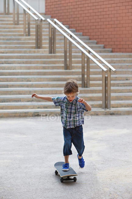 Boy playing with skateboard outdoors — Stock Photo