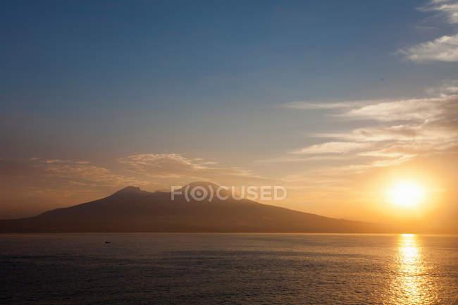 Sun setting over still water — Stock Photo