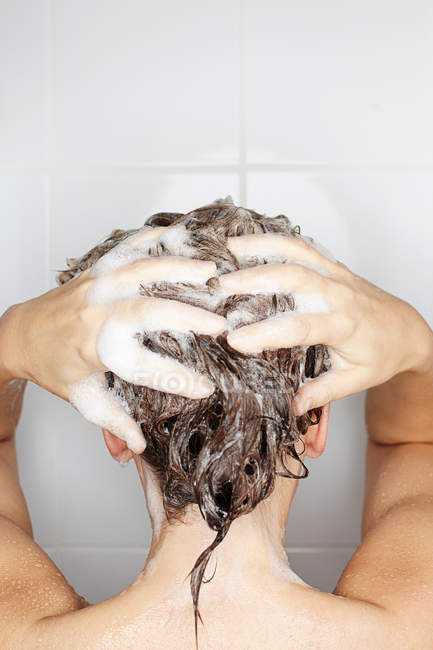 Rear view of woman washing her hair in shower — Stock Photo