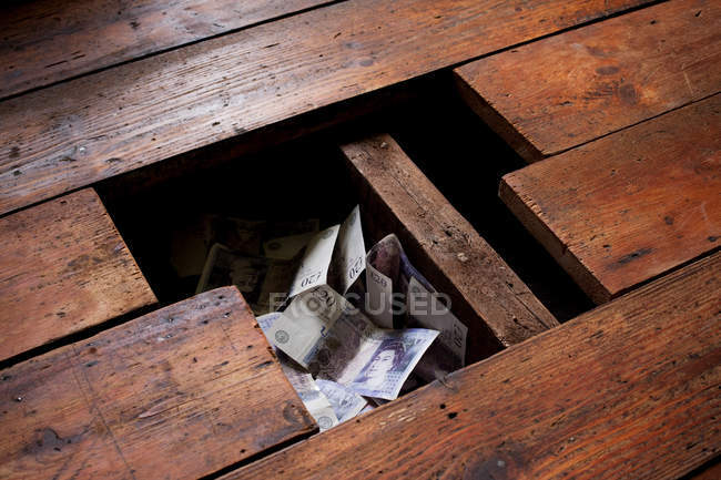 Close up of Money under floorboards — Stock Photo