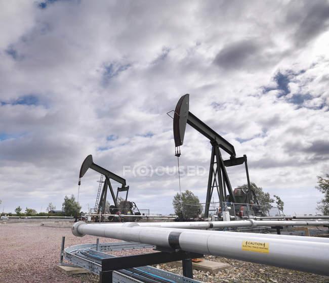 Dos bombas de aceite en tierra - foto de stock