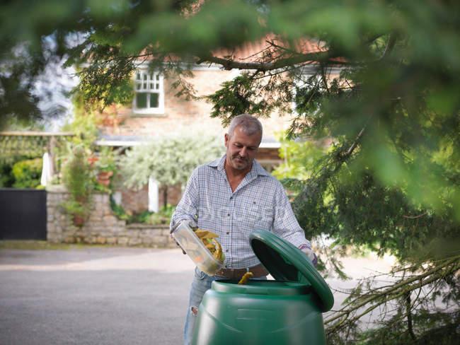 Homme mettant les déchets de cuisine dans la poubelle à compost — Photo de stock