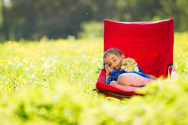 Girl in costume sleeping in chair — Stock Photo