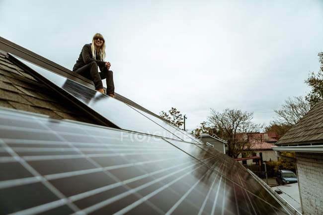 Portrait of mid adult woman sitting on newly solar paneled house roof — Stock Photo