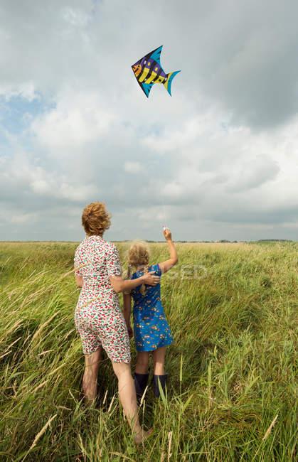 Mãe e filha voando pipa no campo — Fotografia de Stock