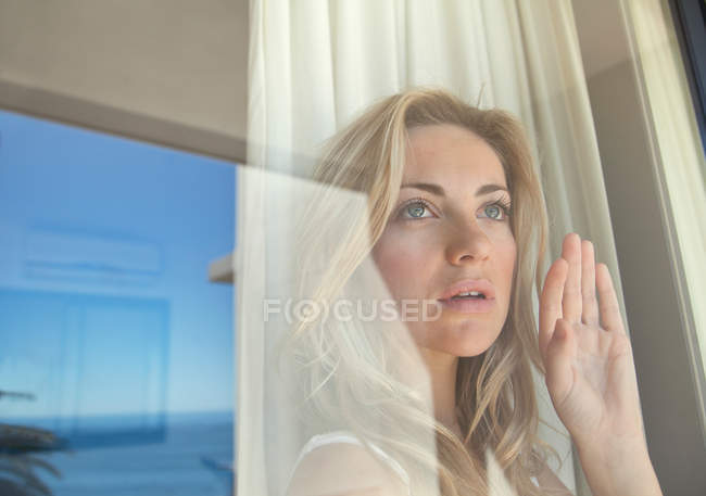 Woman gazing out window, selective focus — Photo de stock