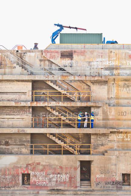 Робітники, які говорять на кроках від сухого док-станції — стокове фото