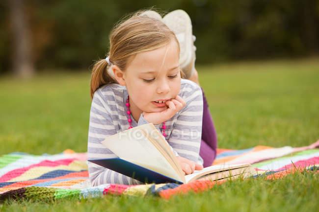 Ragazza lettura libro sulla coperta pic-nic — Foto stock