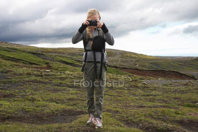 Escursionista scattare foto sul fianco della collina — Foto stock
