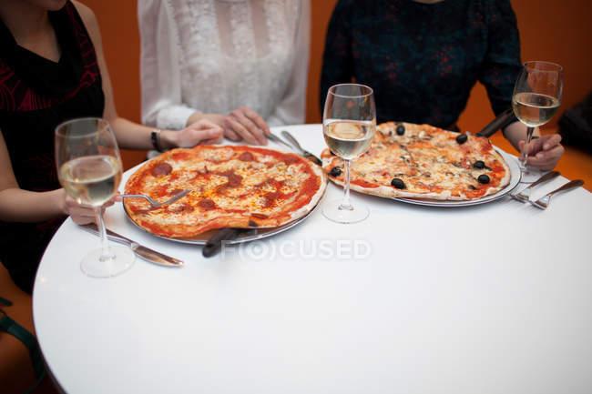 Молодые женщины едят пиццу в ресторане — стоковое фото