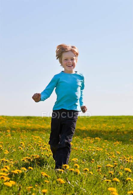 Мальчик бегает по полю цветов — стоковое фото