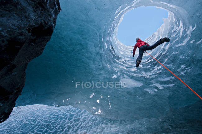 Rear view of climber climbing out of ice cave — Stock Photo