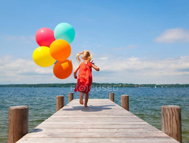 Ragazza che tiene palloncini sul molo di legno — Foto stock
