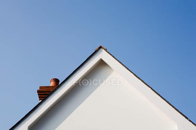 Vista di angolo basso di timpano di una casa contro cielo azzurro chiaro a giorno soleggiato — Foto stock