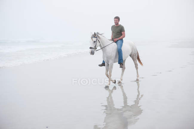 Man riding horse on beach — Stock Photo