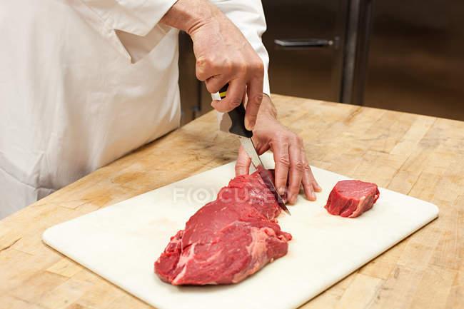 Mâle chef prépare la viande dans la cuisine commerciale, recadrée tir — Photo de stock