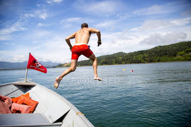 Mid adult man jumping into sea from boat, Nehalem Bay, Oregon, USA — Stock Photo