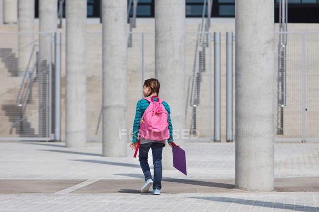 Menina carregando pasta no pátio — Fotografia de Stock