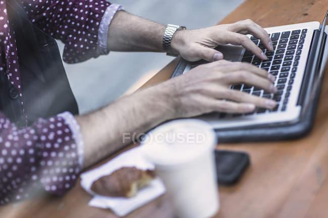 Vista ritagliata di giovane uomo d'affari che digita sulla tastiera del computer portatile al caffè marciapiede — Foto stock