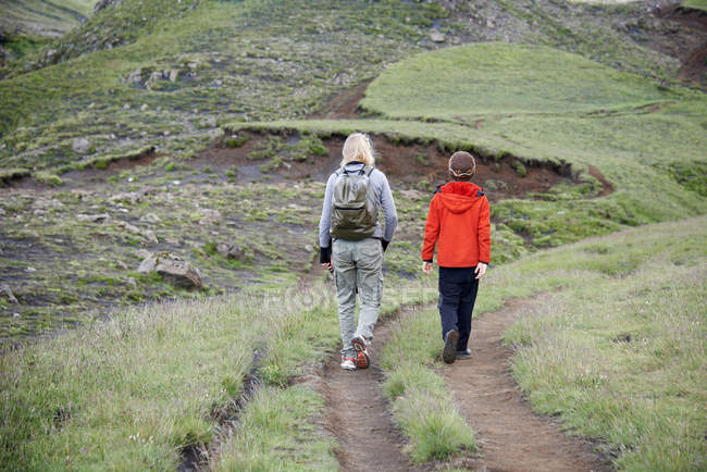 Rear view of mother and daughter hiking on hillside — Stock Photo