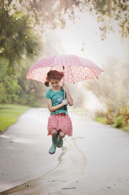Дівчинка тримає парасольку і стрибки калюжі на вулиці — стокове фото