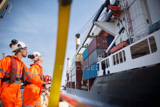 Тягачи на буксире смотрят вверх на контейнерное судно — стоковое фото