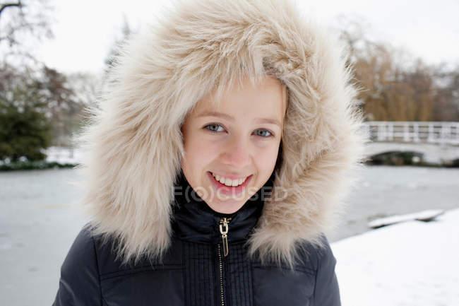 Ragazza sorridente che indossa cappuccio di pelliccia nella neve — Foto stock