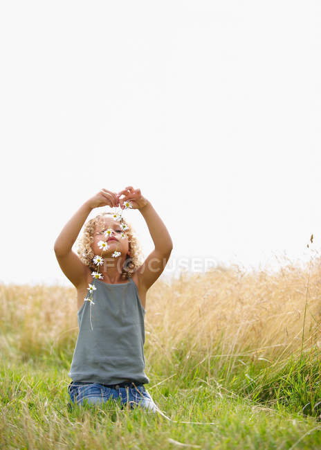 Young girl making a daisy chain in field — Stock Photo