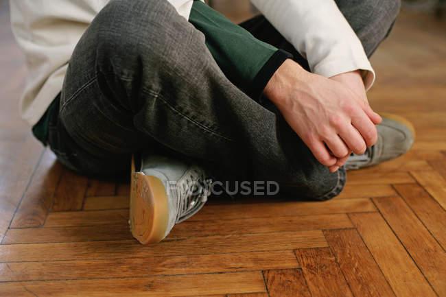 Mann mit gekreuzten Beinen auf dem Boden sitzend — Stockfoto